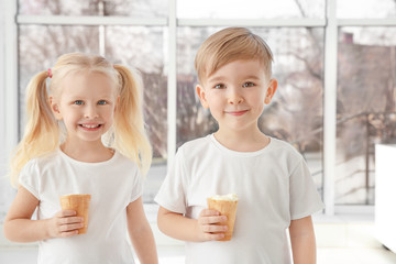 Cute little children eating ice cream on window background