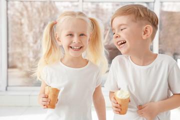 Cute little children eating ice cream on window background