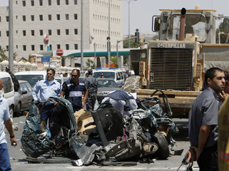 Israeli police officers stand near remains of car at scene of attack in Jerusalem