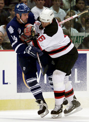 DEVILS' HOLIK CHECKS MAPLE LEAFS HOGLUND OFF HIS SKATES IN GAME 6 OF PLAYOFF SERIES.