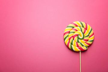 Tasty lollipop on color background