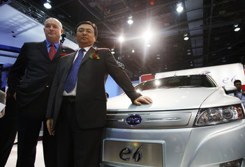 Chairman of MidAmerican Energy Holdings Sokol and BYD president Chuanfu pose beside a BYD E6 in North American International Auto Show Detroit