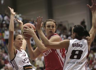 Poland's Kobryn tries to score past Latvia's Tamane and Basko during their European women's basketball championship preliminary round game in Liepaja