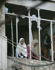 Residents are seen through a damaged window of a building after a bomb attack in Baghdad's al-Ghadeer district