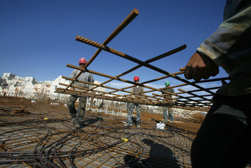 Palestinian labourers work at a construction site in Modiin Illit