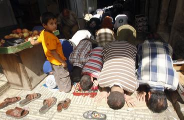 A boy reacts as Palestinian men pray at a market in Nablus