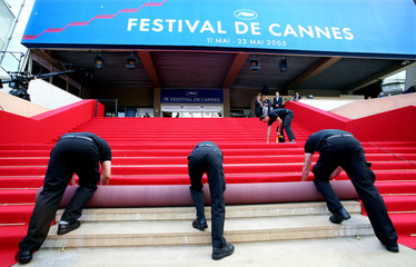 Workmen roll out the red carpet on the steps of the festival palace before the opening evening of ...