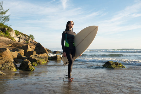 Young female surfer in ocean with surfboard at rocky beach