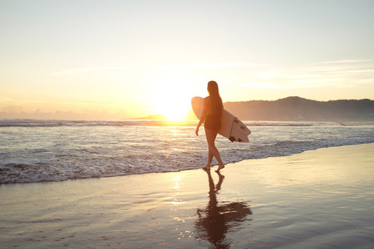 Young female surfer entering the ocean with surfboard at sunset or sunrise