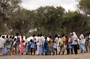Tamil civilians stand in line to receive food in front of tents at the Manik Farm refugee camp located on the outskirts of Vavuniya
