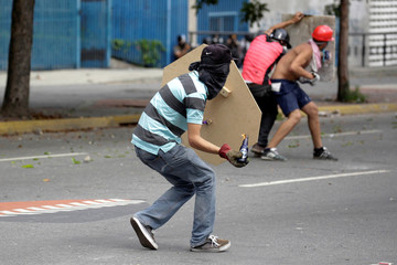 A demonstrator prepares to throw a molotov cocktail during clashes with riot police while rallying against Venezuela's President Nicolas Maduro in Caracas