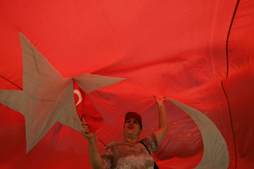 A protester shouts slogans against Turkey's presidential hopeful Foreign Minister Gul as she stands under a Turkish flag during a demonstration in Ankara