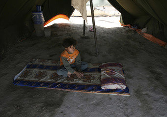 A boy sits under a tent in a refugee camp in Shaab district in Baghdad