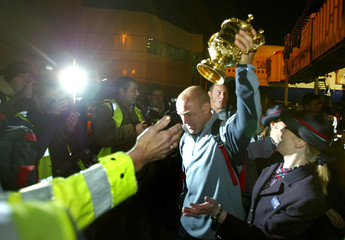 ENGLAND'S NEIL BACK HOLDS THE RUGBY WORLD CUP ALOFT AS HE ARRIVES BACKIN LONDON FROM AUSTRALIA.