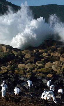VOLUNTEERS CLEANS UP STAINED ROCKS ON SPAIN'S DEVASTED NORTH-WESTCOAST.
