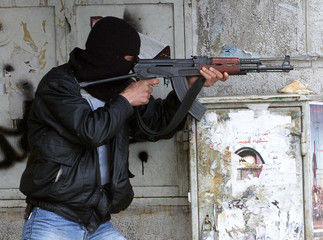 A Palestinian gunman takes a shooting position in the West Bank City of Ramallah March 14, 2002. Pal..