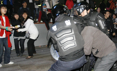 Policemen rush to detain an attendant at an anti-government rally in Seoul