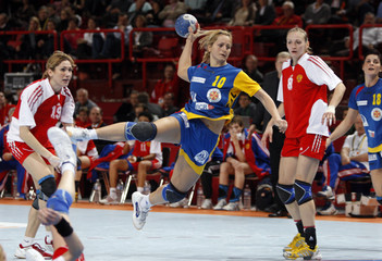 Romania's Stanca-Galca prepares to shoot against between Russia's Dmitrieva and  Andryushina in their women's world handball championship semi-final match at Bercy in Paris