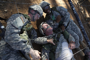 Private Welliver and Private Hubbard drag Private Weaver through an obstacle course during basic training at the Fort Sill Army Post