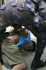 Philippine police arrest a farmer during a protest outside the Department of Agrarian Reform in Manila