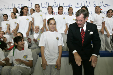 U.S. Secretary of Health and Human Services Leavitt joins students in a fitness training activity in Amman