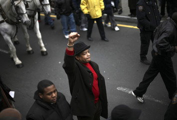 A man raises his fist as a horse-drawn carriage carries the coffin of singer James Brown to the legendary Apollo Theater in Harlem