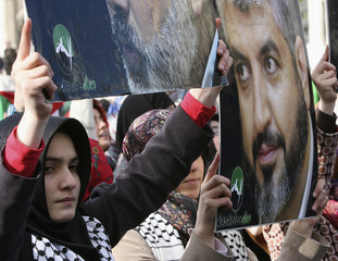 Islamist protesters hold up portraits of Palestinian Hamas leaders Khaled Meshaal and Ismail Haniyeh during a demonstration against Israel in the old city in Istanbul