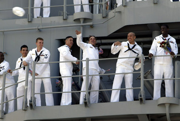 SAILORS FROM USS MOBILE BAY TOSS HATS TO FAMILY AND FRIENDS AS THEYARRIVE HOME FROM WAR.
