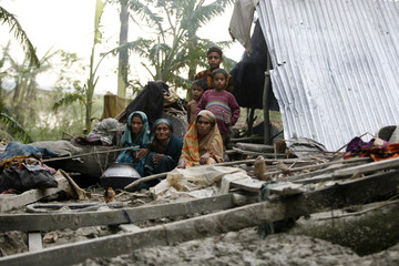 A family lives under the open sky after their home was devastated by storm at Bakerganj