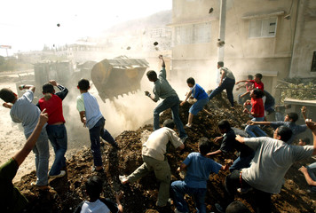 Palestinians throw stones at an Israeli army bulldozer during clashes near Nablus.