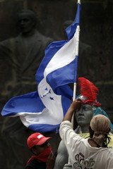 Supporters of Honduras' ousted President Zelaya tape headgear to a statue of national hero Indian chieftain Lempira outside National Congress in Tegucigalpa