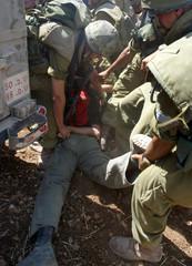 ISRAELI SOLDIERS DRAG AN ISRAELI DEMONSTRATOR NEAR THE CITY OF NABLUS.