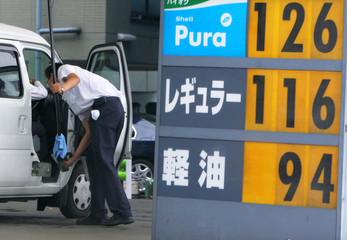 An employee of a petrol station fills petrol for a car in Tokyo.