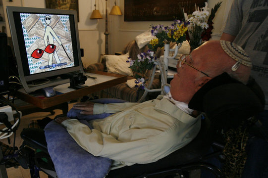 Rahamim Melamed-Cohen is seen near computer screen displaying one of his drawings in Jerusalem