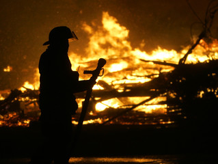 A firefighter watches helplessly as a block of burning buildings are completely engulfed in flames in Galveston