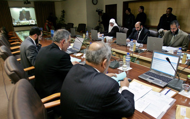 Members of the Palestinian cabinet attend cabinet meeting as Palestinian PM Haniyeh is seen via video-link in Ramallah
