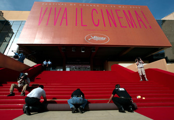 Workmen lay the red carpet on the steps of the Festival Palace during final preparations for the ope..