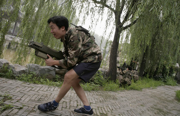 "A customer of Xuelang Outdoor Sports Club uses a laser gun during a ""Counter-Strike"" game in Beijing"