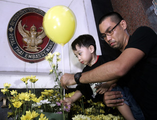Member of Black & White Movement places flowers outside Thai embassy during a rally in Manila