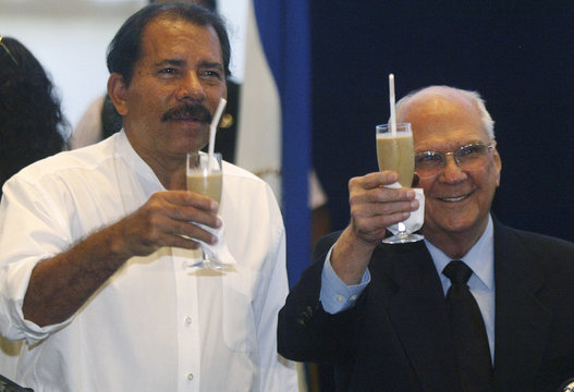 Sandinista Front leader and Nicaragua's President-elect Ortega drinks iced coffee with President Bolanos in Managua