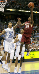 FSU's Douglas shoots under pressure from UNC's Stepheson and Terry during NCAA basketball tournament in Tampa
