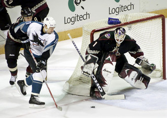 COYOTES GOALIE BURKE STOPS SHOT BY SHARKS WING THORNTON IN WESTERNCONFERENCE QUARTERFINALS.