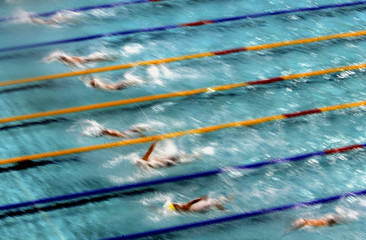 Swimmers power during 100 metre backstroke semi-final in Athens' Aquatic centre on the second day of ...