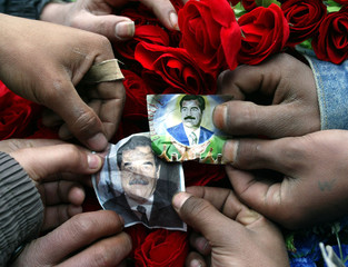 Palestinian refugees stick pictures of Iraqi President Saddam Hussein on a bunch of red roses sold b..