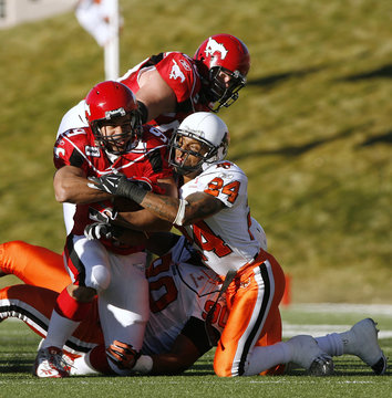 BC Lions Korey Banks and Aaron Hunt tackles Calgary Stampeders Jon Cornish during the first half of their CFL football game against in Calgary.