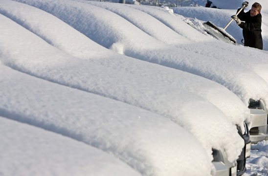 A car salesman removes snow from coverd cars in Lindau at Lake Constance