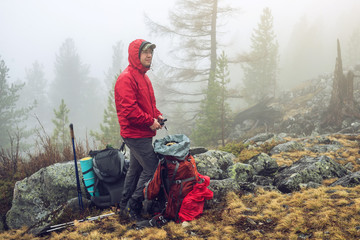 Hiker travels in the mountain forest in the mist with a backpack. Concept of travel and Hiking in wild places of nature