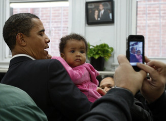 U.S. President-elect Barack Obama has his picture taken with a little girl at Ben's Chili Bowl Restaurant in Washington