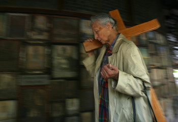 A religious believer carries a cross at the Graciousnesses chapel in Altoetting