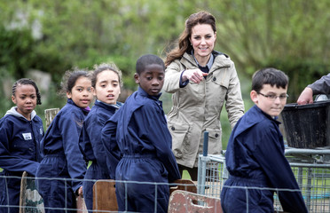 """Britain's Catherine, The Duchess of Cambridge jokes with children from Vauxhall primary school after they attempted to herd a pig into a pen during a visit to a """"Farms for Children"""" farm in Gloucestershire"""